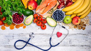 healthy foods on a table and a heart stethoscope