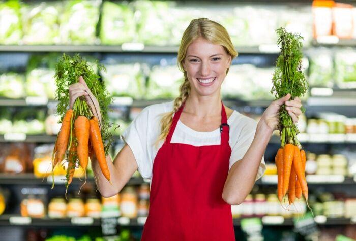 Smiling-female-staff-holding-organic-carrots