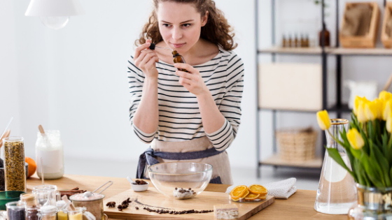 woman smelling and making mixing her own essential oils