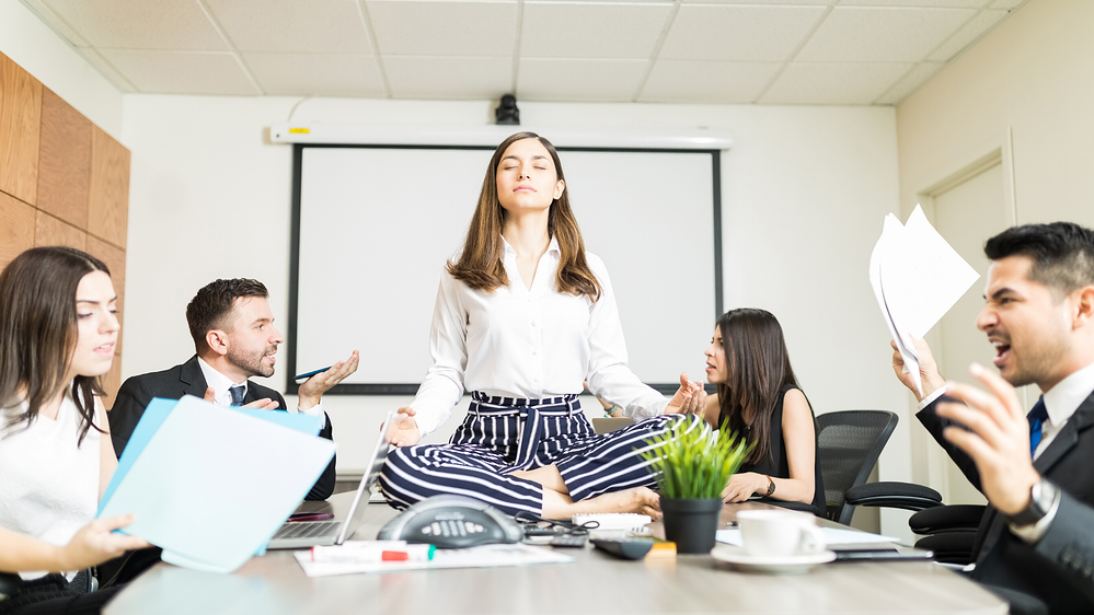 Woman meditating during chaotic office meeting and staying calm and centered