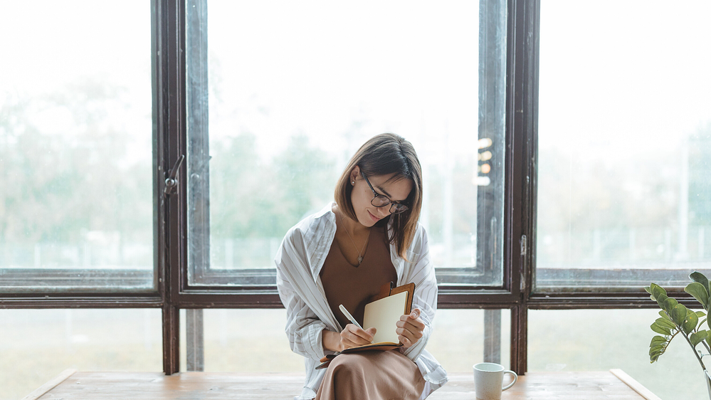 woman writing down her feelings and being mindful of emotional triggers