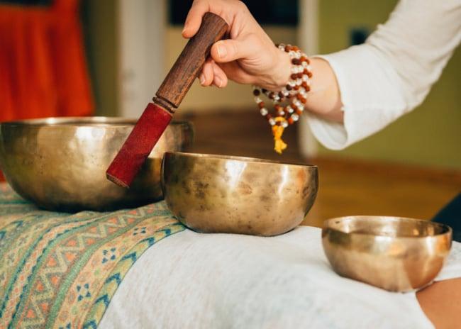 woman playing Tibetan bowl mediation music