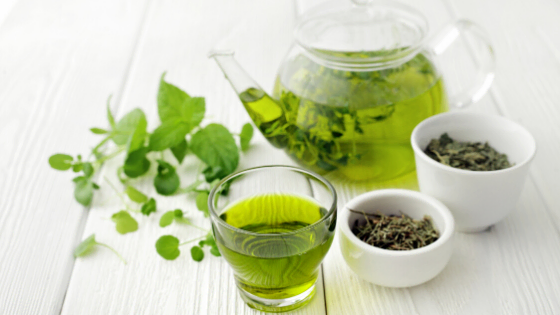 fresh green tea with teapot and leaves