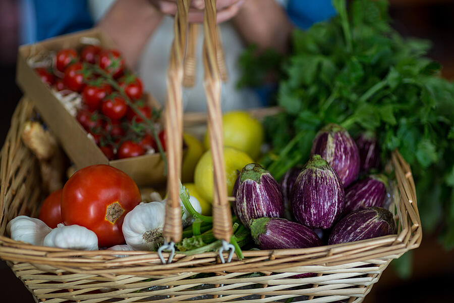 Close-up of female staff holding basket of vegetables in organic section of supermarket