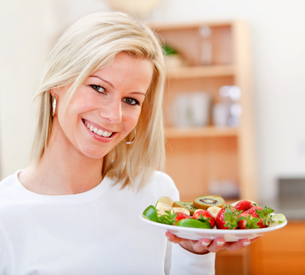 Healthy eating woman with fruits and smiling