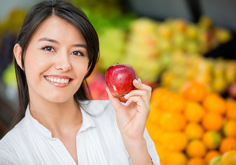 Woman buying organic apples at the supermarket
