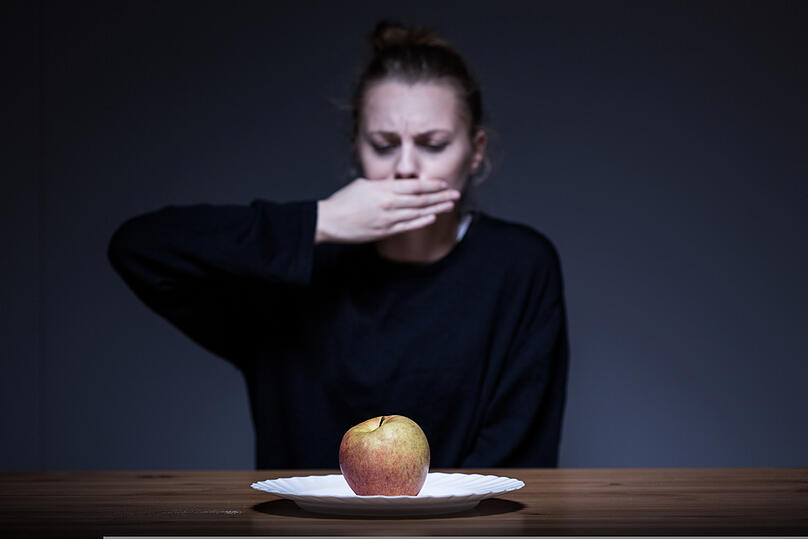 Woman with anorexia refusing to eat an apple