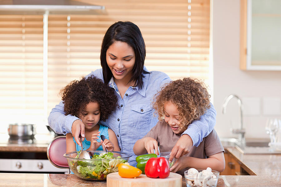Young mother and daughters preparing salad in the kitchen together