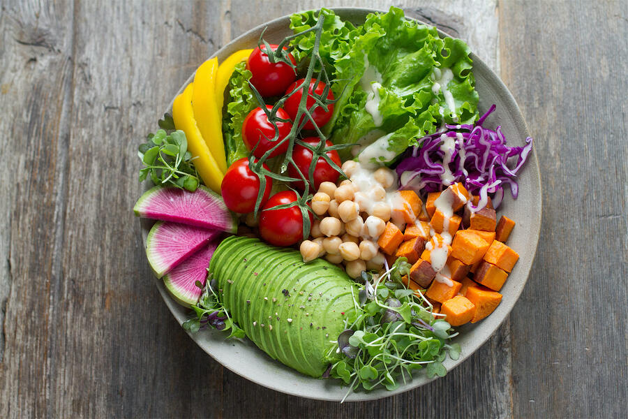 fresh vegetable salad with chickpeas and raw veggies with dressing in bowl