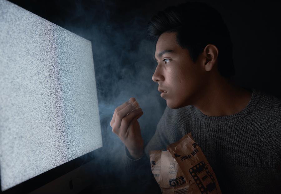 teen mindless watching tv eating junk food