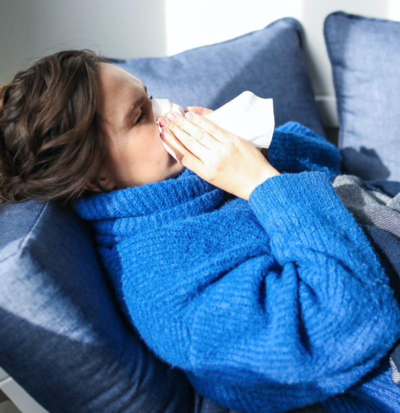 Woman sneezing in tissue with cold flu sick