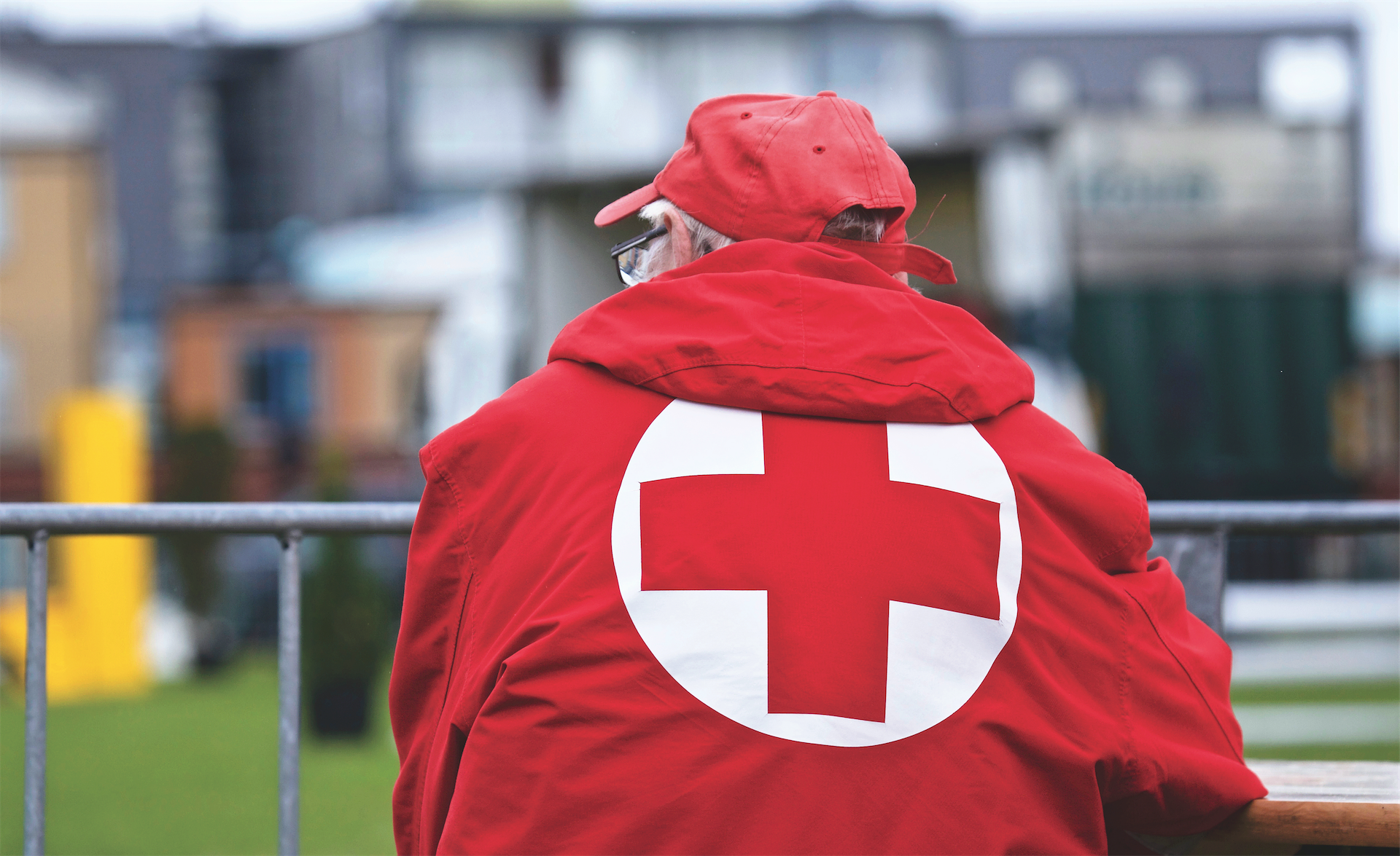 Older man volunteering during crisis red cross