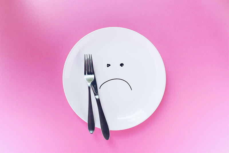 plate with sad face, knife and fork and pink background
